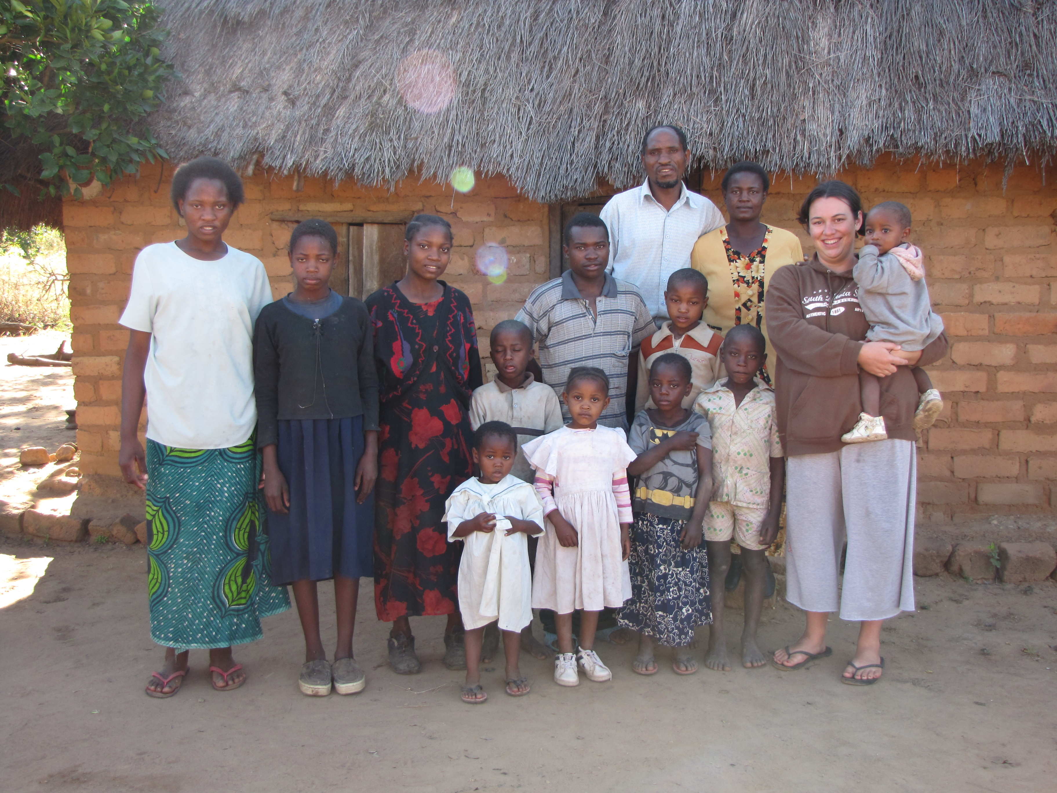 christa and her peace corps host family in front of the main family house