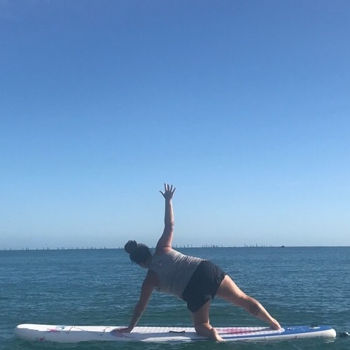 christa doing yoga on a paddleboard